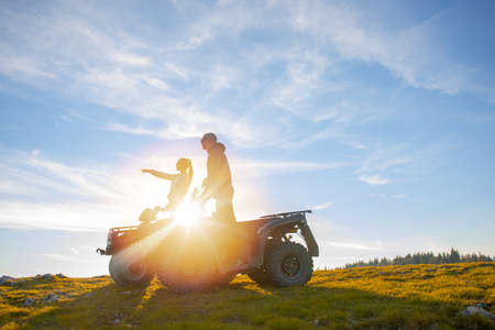 Beautiful couple is watching the sunset from the mountain sitting on atv quadbike