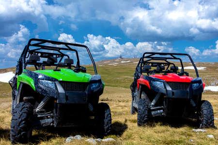 Estacionado ATV y UTV, buggies en el pico de la montaña con nubes y cielo azul en segundo plano. Foto de archivo