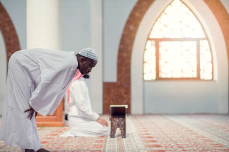 Two religious muslim man praying together inside the mosque