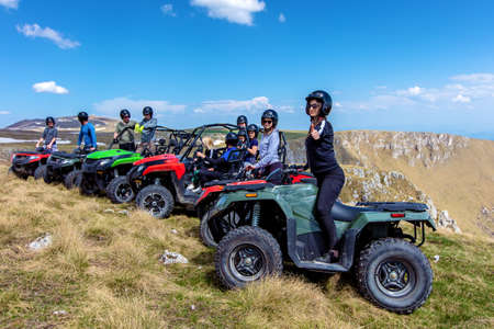 Friends driving off-road with quad bike or ATV and UTV vehicles Stock Photo
