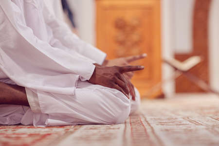 Two religious muslim man praying together inside the mosque.