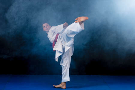 Pre-teen boy doing karate on a black background with smoke