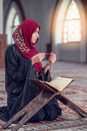 Young muslim woman praying with rosary in mosque