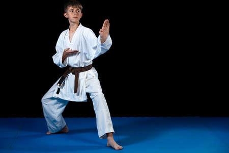 Ragazzo giovane formazione karate su sfondo nero