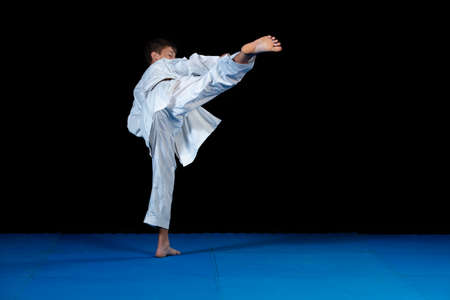 Young boy training karate on black background