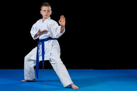 Pre-teen boy doing karate on a black background