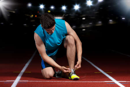 young athletic male sitting on running track and stretching at sports stadium Foto de archivo