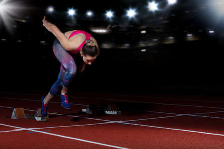 woman sprinter leaving starting blocks on the athletic track. exploding start on stadium with reflectors Stock Photo