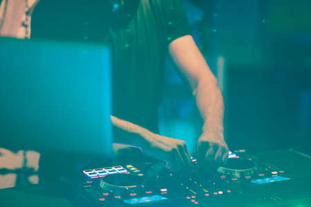Dj mixes the track in the nightclub at party. DJ hands in motion Stock Photo - 106895440