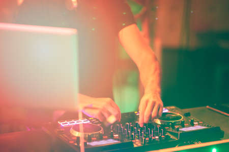 Dj mixes the track in the nightclub at party. DJ hands in motion Stock Photo