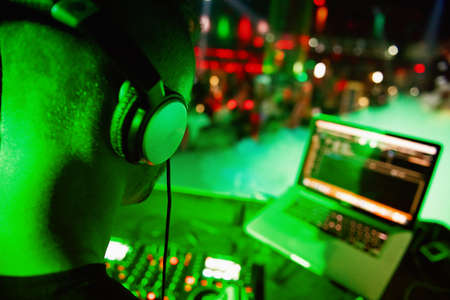 Dj mixes the track in the nightclub at party. DJ hands in motion Stock Photo - 106895447
