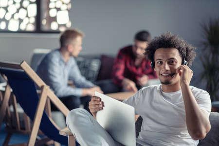Riendo desarrollador de software afroamericano hipster en la computadora en la oficina de la empresa de inicio