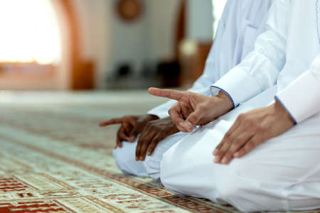 Muslim men praying with holy books in mosque Stock Photo