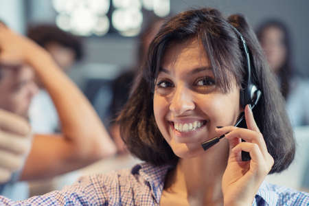 Beautiful phone operator Arab woman working in modern startup office