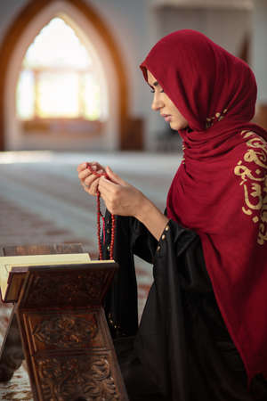 Young praying woman falling on knees in mosque