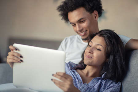 Young attractive diverse couple browsing internet, using laptop computer, smiling.