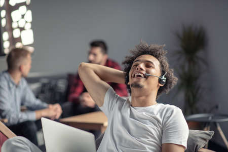 Laughing african american hipster software developer at computer at office of startup company Stock Photo