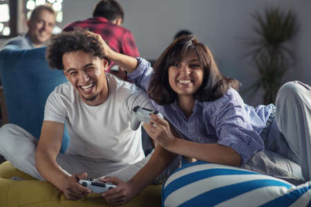 Happy couple playing video games at the modern startup office