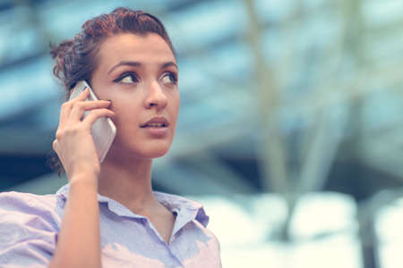 Young woman busy with calling, chatting on the cell phone side view portrait. Banque d'images