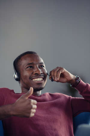 Emotional dark skinned male freelancer celebrating completed project successfully.