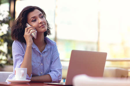 Businesswoman Using Phone While Working In Coffee Shop Stock Photo