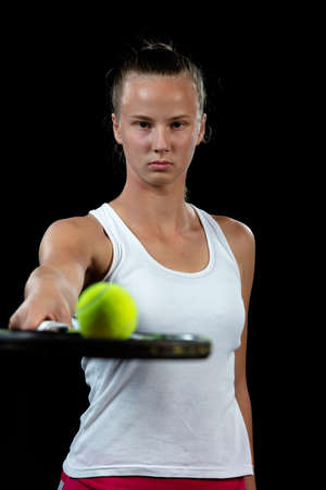Young woman on a tennis practice. Beginner player holding a racket, learning basic skills. Portrait on black background