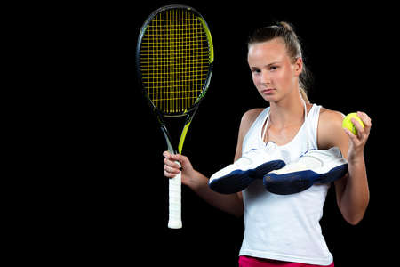 Young woman on a tennis practice. Beginner player holding a racket, learning basic skills. Portrait on black background. Reklamní fotografie