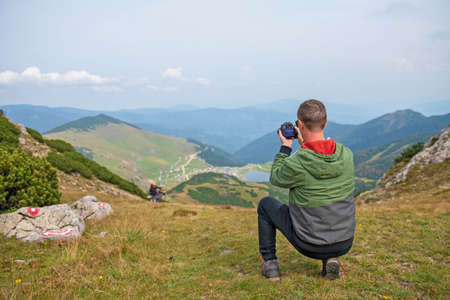 Male tourists are photographing a lake that is a natural attraction. Concept for Travel.