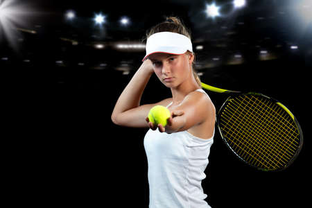 Beautiful girl tennis player with a racket on dark background with lights