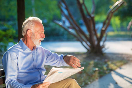 Portrait of a senior man reading newspapers in the park. Stock Photo