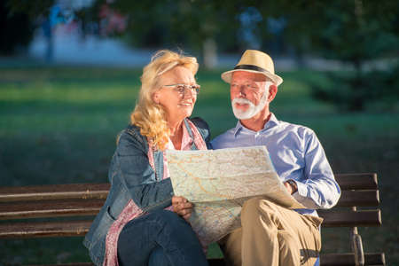 Portrait of happy man and woman reading map while sitting on a park bench. Senior couple on vacation using city map.