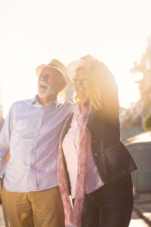 Happy cheerful senior couple of tourists with map and city guide walking on street Stock Photo