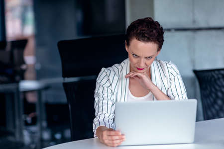 A young businesswoman sits behind her laptop computer frowning with her head in her hands because of a problem at work