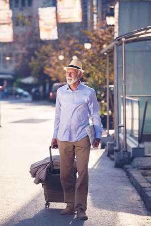 Happy Senior tourist man with suitcase in city.