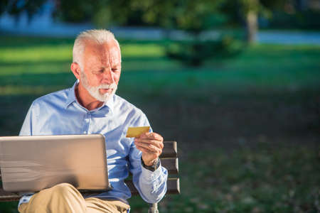 Old male sitting on bench and surfing net on laptop in park, shopping online concept Imagens