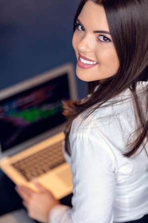 Portrait of businesswoman using laptop while colleague seen in background at creative office.