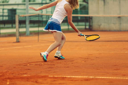 Beautiful female athlete with perfect body posing on tennis court, close up Banco de Imagens