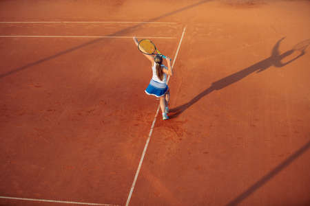 Woman playing tennis on clay court, with sporty outfit and healthy lifestyle