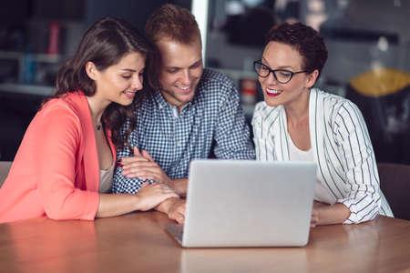 Asesor de inversiones dando una presentación a una amigable pareja joven sonriente sentada en su escritorio en la oficina