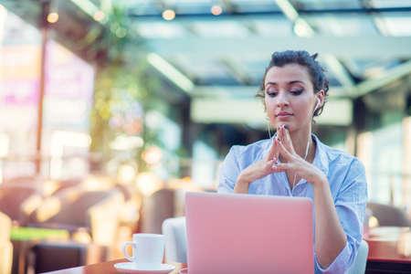 Bild der glücklichen Frau mit Laptop beim Sitzen im Café. Junge Frau, die in einem Café sitzt und an Laptop arbeitet.