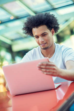 Serious Afro American male student in T-shirt sitting at cafeteria drinking takeaway coffee working at his project using laptop