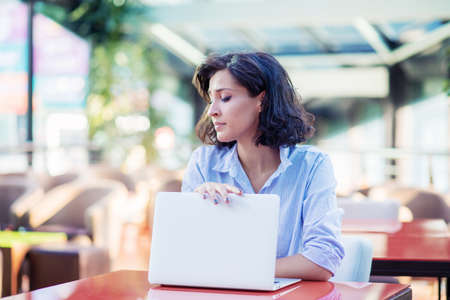 Contemplated young woman in cafe with laptop Imagens