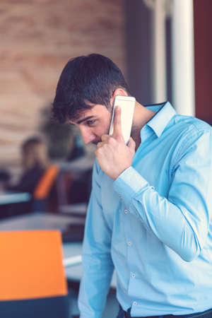 Young smiling businessman calling on phone at office. Stok Fotoğraf - 133949736