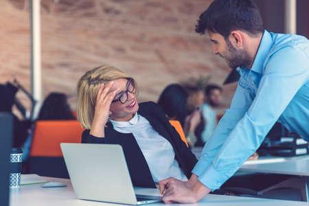 Szczęśliwi partnerzy biznesowi pracujący na laptopie. Praca zespołowa, koncepcje coworkingowe.