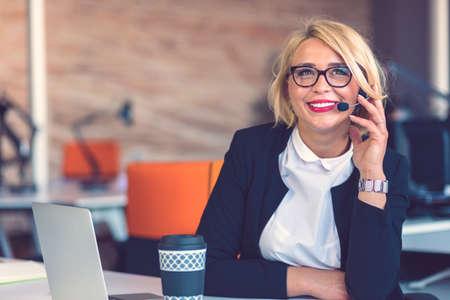 Representante de servicio al cliente en el trabajo. Hermosa mujer joven en auriculares trabajando en la computadora