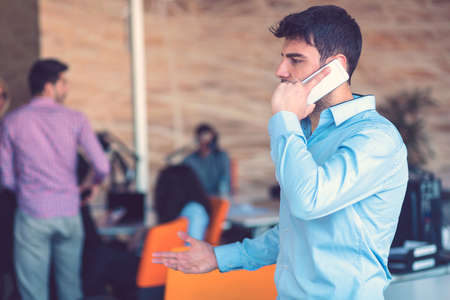 Young smiling businessman calling on phone at office. Stok Fotoğraf - 133950308