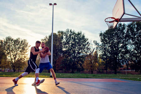 Two street basketball players playing hard on the court.