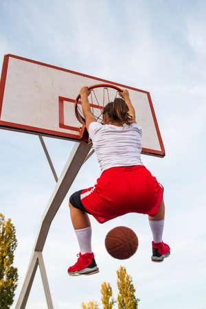 Females playing basketball on street court. Woman streetball player making slam dunk in a basketball game