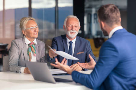 Positive aged couple consulting with insurance agent Stock fotó