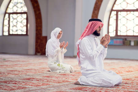African Muslim Couple Praying inside of beutiful mosque